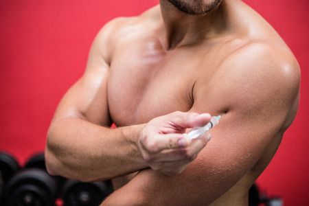 hormone  male: Muscular man injecting steroids in crossfit gym
