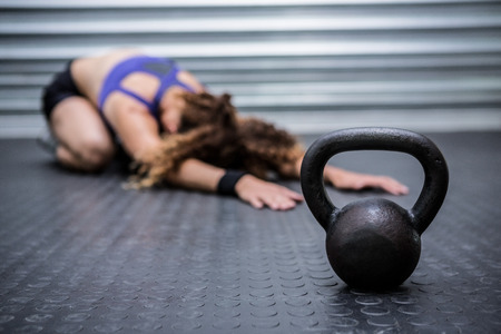 kettlebell: Muscular woman stretching in crossfit gym