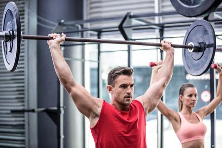 bodybuilder: Dos culturistas jóvenes haciendo el levantamiento de pesas en el gimnasio crossfit