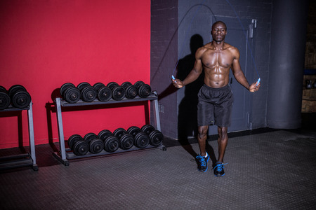 Young Bodybuilder doing jumps over a rope in the crossfit gym
