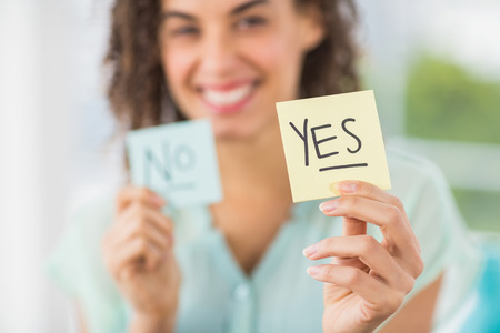 Portrait of a smiling businesswoman holding yes and no sticks Banque d'images