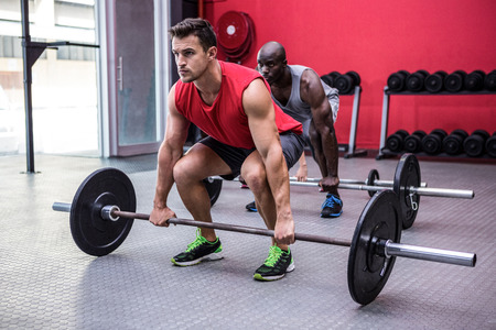 ini: Three young Bodybuilders doing weightlifting ini the crossfit gym