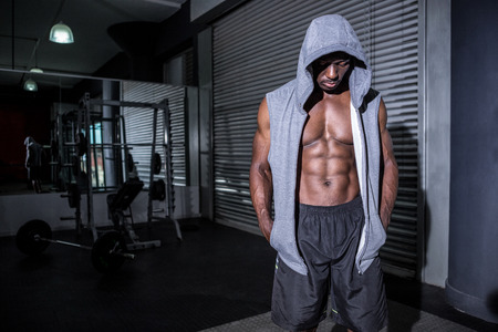 crossfit: Young Bodybuilder in a hoodie looking at the hoodie in the crossfit gym Stock Photo
