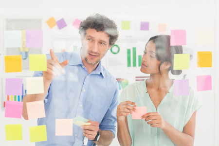 inquiring: Puzzled business team looking sticky notes on the wall in the office