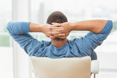 finger crossed: Back view of a relaxed creative businessman lying in a chair Stock Photo
