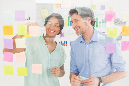 Puzzled business team looking post its on the wall in the office Stock Photo