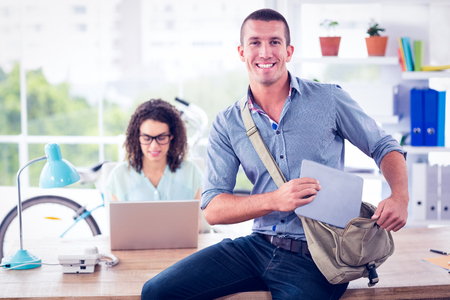 tidying: Creative businessman looking at the camera while tidying tablet in the bag Stock Photo