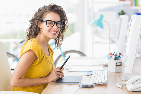 Creative young businesswoman looking at the camera in the office