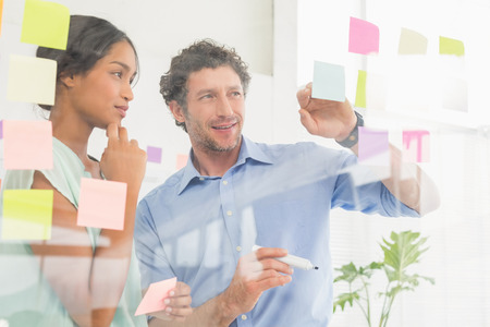 inquiring: Puzzled business team looking post its on the wall in the office Stock Photo