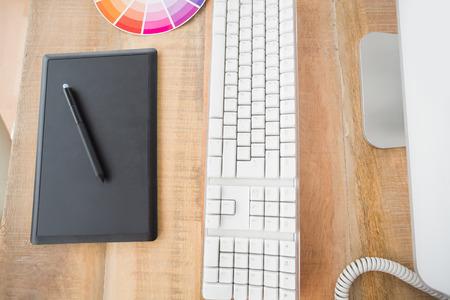 Vue vers le haut du bois de table avec une tablette graphique et l'ordinateur