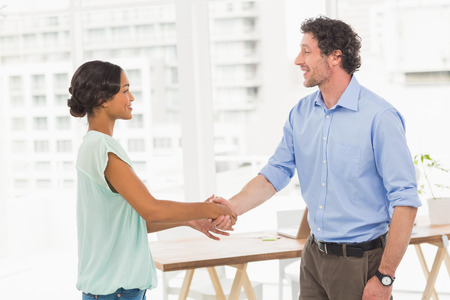 casual business: Casual business partners shaking their hands in the office Stock Photo