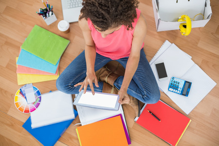 scrolling: Upward view of young creative businesswoman scrolling on tablet Stock Photo