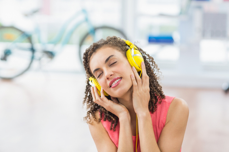 woman hands up: Young creative businesswoman enjoying music with eye closed