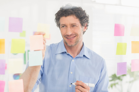 inquiring: Puzzled businessman looking post its on the wall in the office
