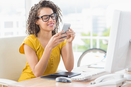Smiling young businesswoman sending a text message in the office Stock Photo