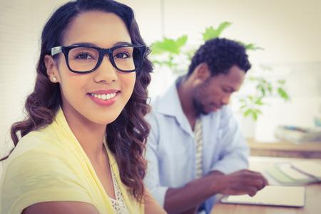 junge nackte frau: Recht junge Geschäftsfrau lächelnd in die Kamera mit einem Geschäftsmann hinter ihr im Büro. Lizenzfreie Bilder