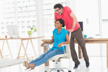 swivel chair: Smiling partners playing together with swivel chair in the office