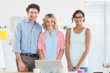 casual business: Casual business team looking at laptop together in creative office Stock Photo