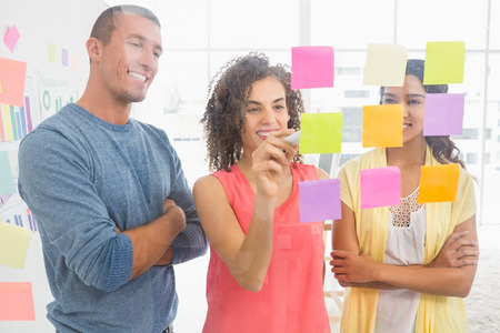 sticky notes: Smiling coworkers writing on sticky notes in the office Stock Photo