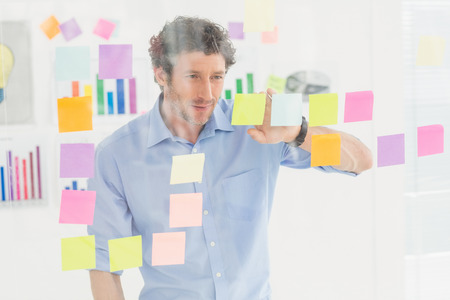 postit: Creative businessman looking at post-it in the office