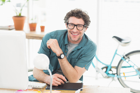 graphic designers: Cheerful graphic designer using a graphics tablet in a modern office Stock Photo