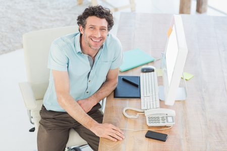 creative artist: Smiling designer working on his computer in the office