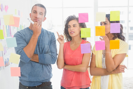 sticky notes: Concentrated coworkers pointing sticky notes in the office Stock Photo