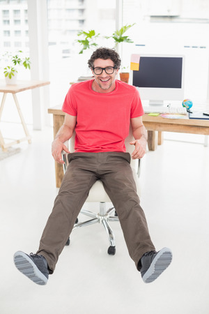 swivel chair: Handsome businessman sitting on a swivel chair and using his laptop against a white screen
