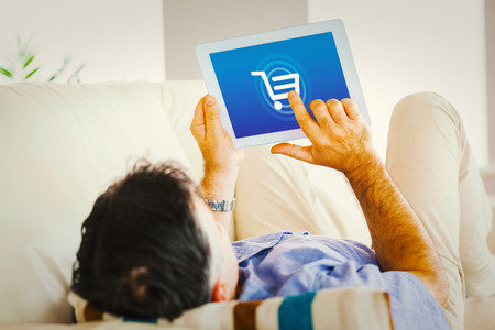 online shopping cart: Man laying on sofa using a tablet pc against trolley Stock Photo