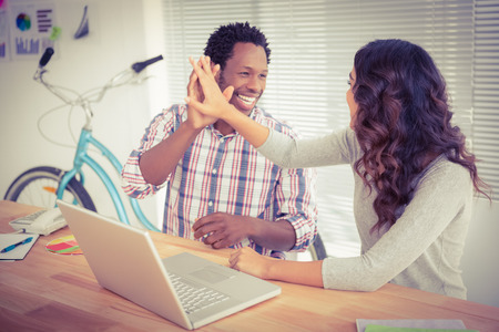 high: Young business people smiling at each other in the office Stock Photo