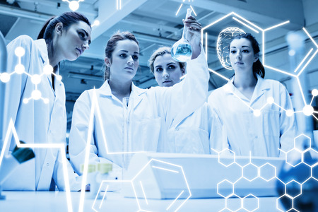 biochemist: Chemistry students looking at a liquid against science graphic Stock Photo