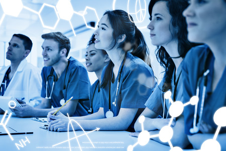 estudiantes medicina: Ciencia gr�fica contra los estudiantes de medicina de escucha sentado en el escritorio