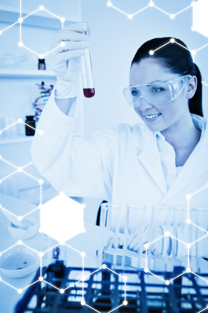 haematologists: Science graphic against pretty redhaired woman holding a test tube Stock Photo