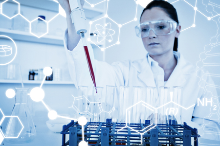 haematologists: Science graphic against pretty female biologist holding a manual pipette with sample from test tubes