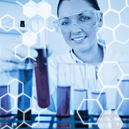 micropipette: Science graphic against gorgeous redhaired female holding a test tube Stock Photo