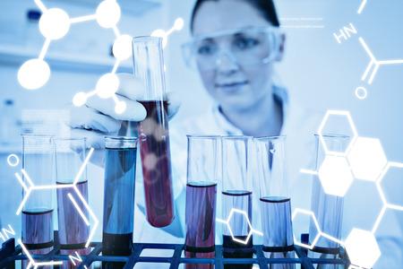 laboratorio: Ciencia gr�fico contra la hermosa mujer pelirroja que sostiene un tubo de ensayo