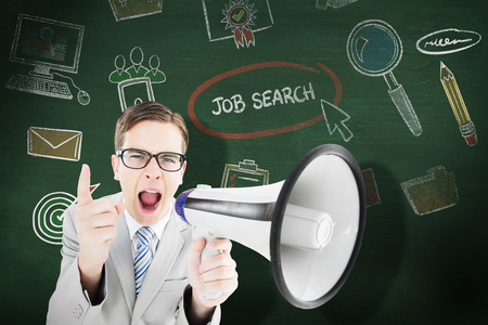 businessman using a megaphone: Geeky businessman shouting through megaphone against green chalkboard