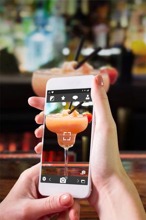 tomando refresco: Mano que sostiene teléfono inteligente contra la cerca en el daiquiri congelado colorido