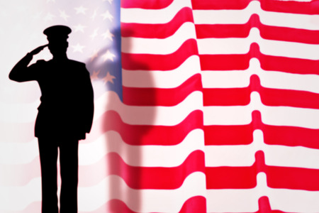 solider: solider silhouette  against rippled us flag Stock Photo