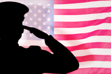 soldier silhouette  against rippled us flag