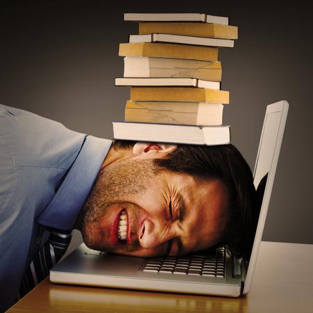 over worked: Businessman resting head on keyboard against grey vignette