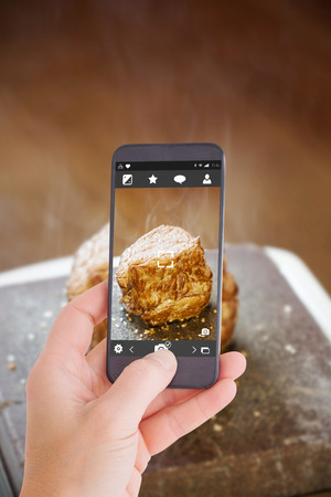 sizzling: Female hand holding a smartphone against steak sizzling on hot stone plate Stock Photo
