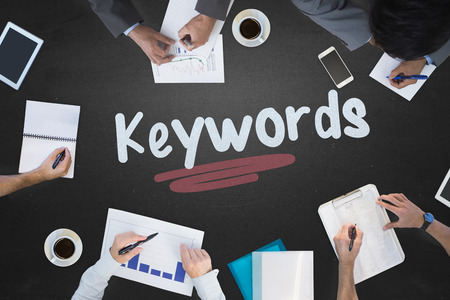 The word keywords and business meeting against blackboard Stock Photo