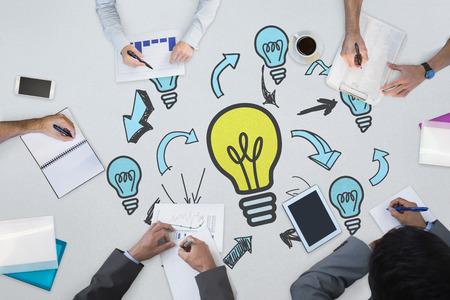 innovating: Business meeting against light bulbs Stock Photo