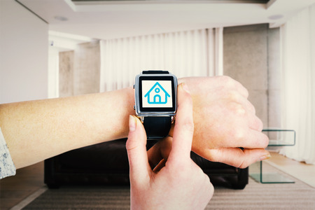 domestic room: Woman using smartwatch against brown leather couch in a modern living room Stock Photo