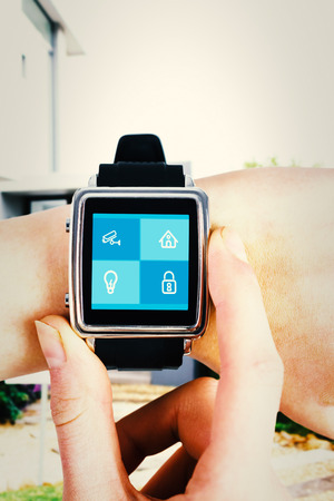 control centre: Woman using smartwatch against home control centre Stock Photo