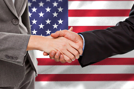 patriotism: Close up of two businesspeople shaking their hands against black wall Stock Photo