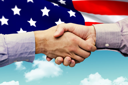 old flag: Hand shake in front of wires against blue sky