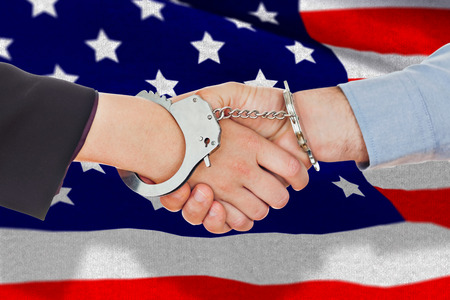 restraining: Business people in handcuffs shaking hands against black wall Stock Photo