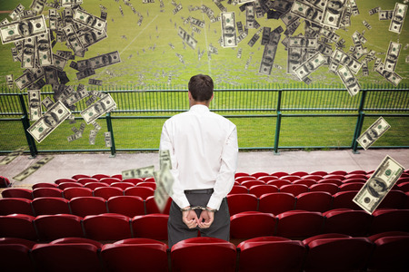 restraining device: Rear view of young businessman wearing handcuffs against red bleachers looking down on football pitch Stock Photo